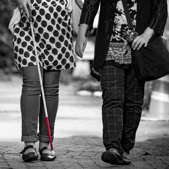 Blind person walking with her friend