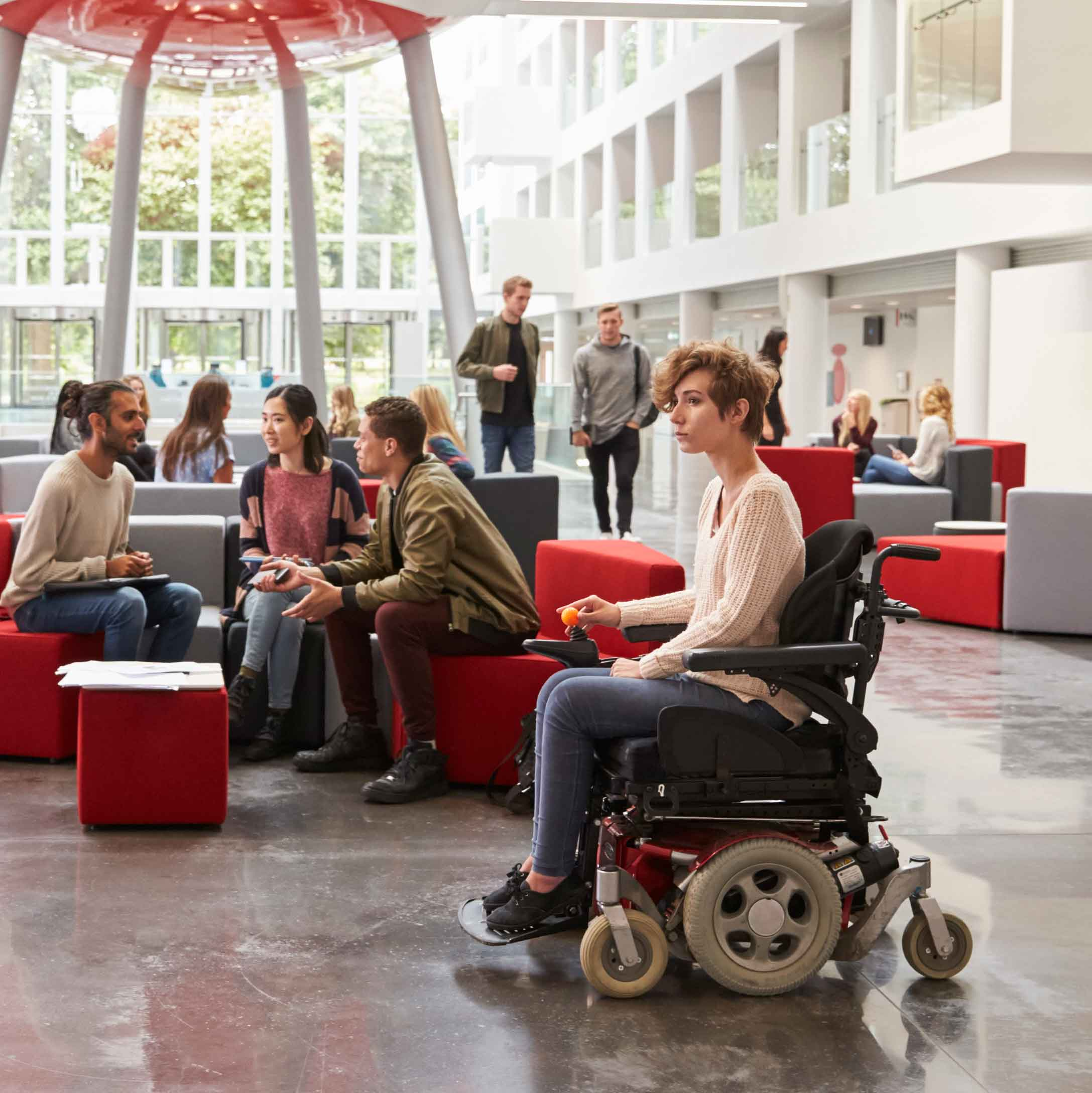 Student in wheelchair and colleagues in university lobby